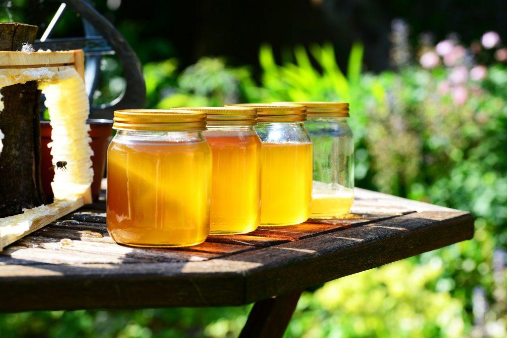 Honiggläser auf Holztisch im Garten